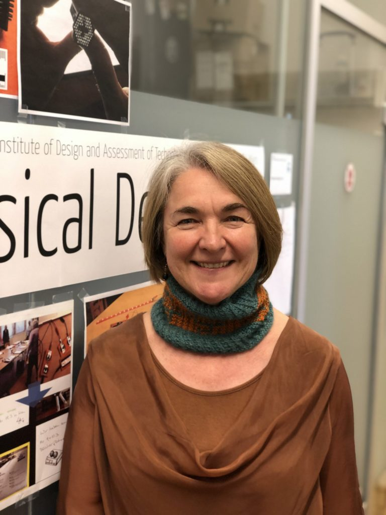 A photo of Geraldine Fitzpatrick, one of the CHI 2019 General Chairs, wearing the finished knitted cowl.
